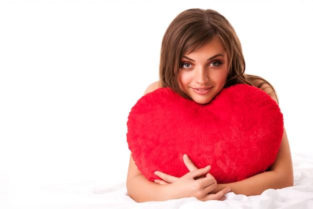 Joven hermosa mujer morena en vestido beige sentado y sosteniendo gran corazón de juguete rojo en manos sobre fondo blanco
