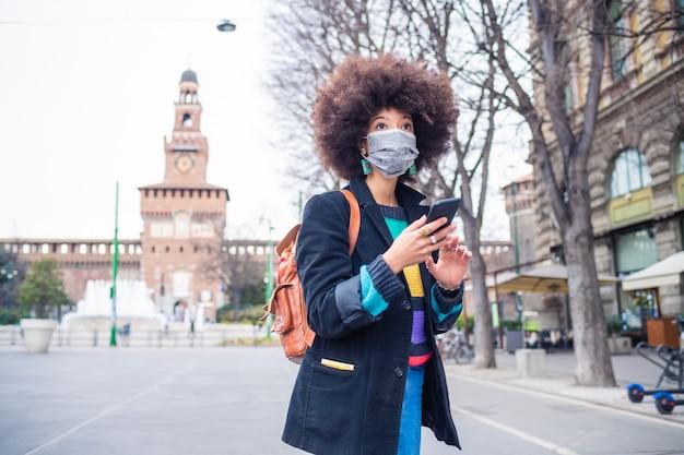Joven hermosa mujer multiétnica con máscara médica con smartphone