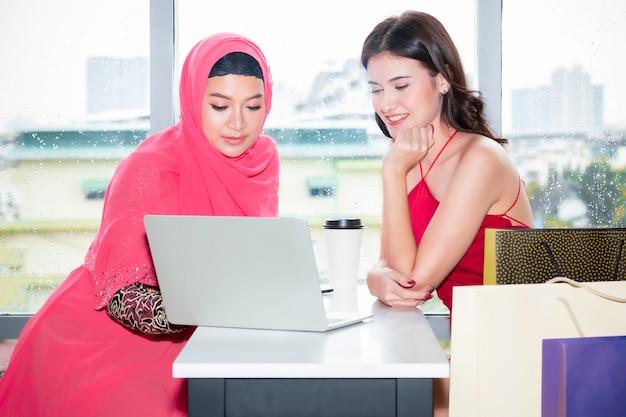 Joven hermosa mujer musulmana y amistades caucásicas con bolsas de compras y tableta disfrutando de compras en la cafetería. señora eligiendo comprar en línea.