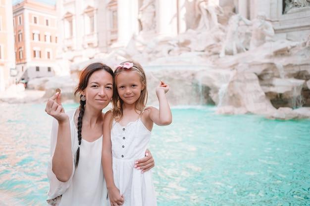 Joven hermosa mujer y niña cerca de la fuente fontana di trevi