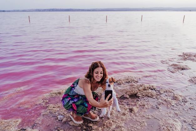 Joven hermosa mujer de pie junto a un lago rosa con su perro