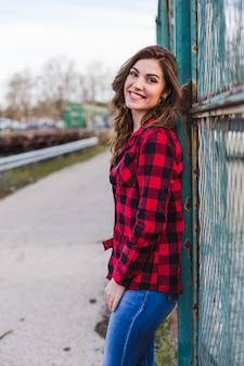 Joven hermosa mujer de pie junto a una valla.