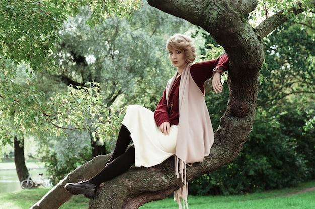 Joven hermosa mujer posando en un árbol.