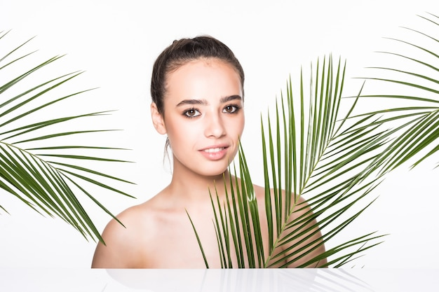 Joven hermosa mujer posando con hojas de palma verde
