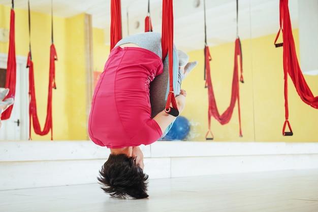 Joven hermosa mujer practicando yoga volar con una hamaca en estudio.