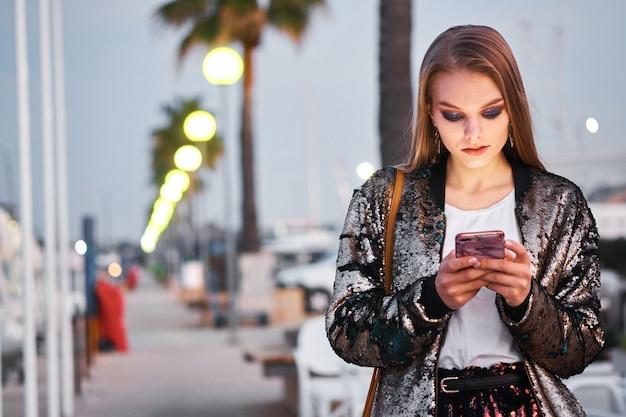 Joven hermosa mujer rubia caminando y escribiendo mensajes sms