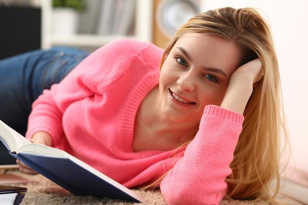 Joven hermosa mujer rubia se encuentran en el suelo, leer el libro