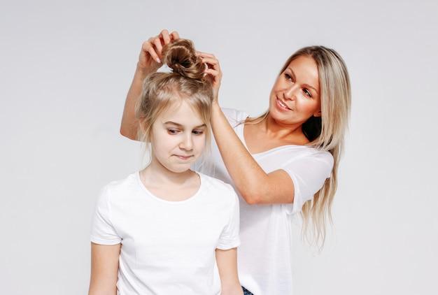 Joven hermosa mujer rubia hacer peinado para niña. ocio conjunto de madre e hija. aislado sobre fondo blanco