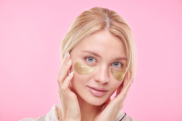 Joven hermosa mujer rubia con parches debajo de los ojos revitalizantes dorados manteniendo las manos en su rostro radiante