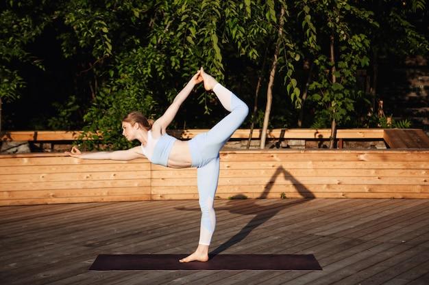 Joven hermosa mujer rubia practicando yoga afuera al amanecer