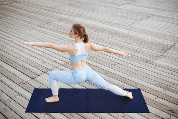 Joven hermosa mujer rubia practicando yoga afuera