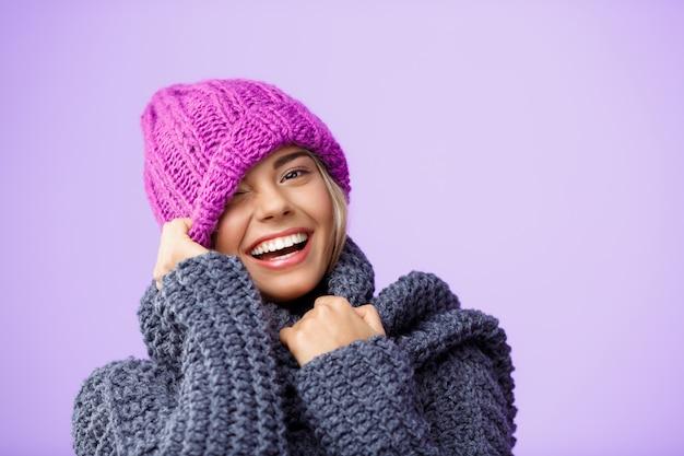Joven hermosa mujer rubia en sombrero de punto y suéter sonriendo guiñando un ojo en violeta.