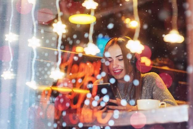 Joven hermosa mujer sentada en la cafetería, tomando café. modelo escuchando música.