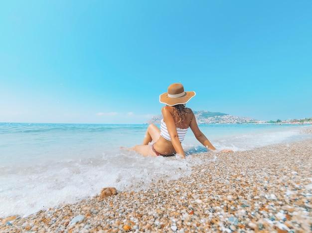 Joven hermosa mujer está sentada en el costo del mar y disfrutando del paisaje de olas.