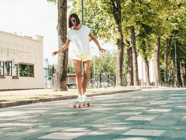Joven hermosa mujer sexy hipster sonriente en gafas de sol. chica de moda en camiseta y pantalones cortos de verano. mujer positiva montando monopatín centavo azul en la calle