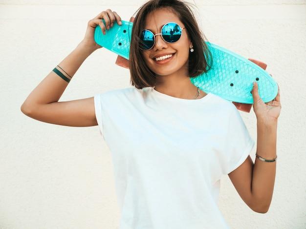 Joven hermosa mujer sexy hipster sonriente en gafas de sol. chica de moda en camiseta y pantalones cortos de verano. mujer positiva con patín azul centavo posando en la calle cerca de la pared blanca