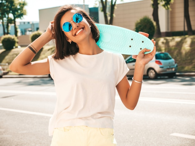 Joven hermosa mujer sexy hipster sonriente en gafas de sol. chica de moda en camiseta y pantalones cortos de verano. mujer positiva con patín azul centavo posando en el fondo de la calle