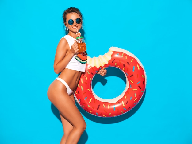Joven hermosa mujer sexy sonriente en gafas de sol. chica en calzoncillos blancos de verano y tema con colchón inflable donut lilo. hembra positiva volviéndose loca.