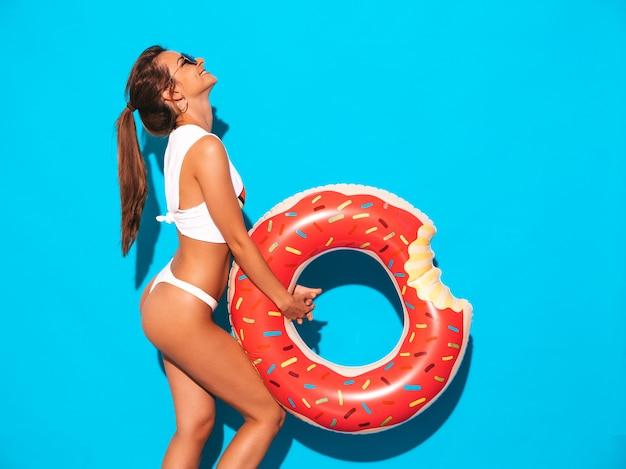 Joven hermosa mujer sexy sonriente en gafas de sol. chica en calzoncillos blancos de verano y tema con colchón inflable donut lilo.