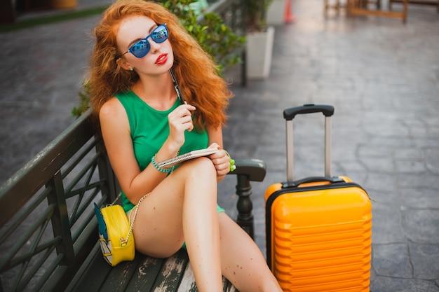 Joven hermosa mujer sexy, traje hipster, cabello rojo, viajero, tapa verde, maleta naranja, tomando notas, diario de viaje