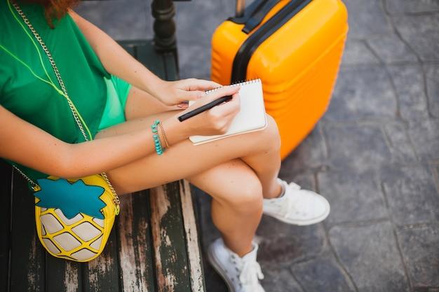 Joven hermosa mujer sexy, traje hipster, viajero, maleta naranja, haciendo notas en el libro de diario de viaje, vacaciones de verano, aventura, viaje, colorido, manos escribiendo, bolígrafo, detalles de cerca