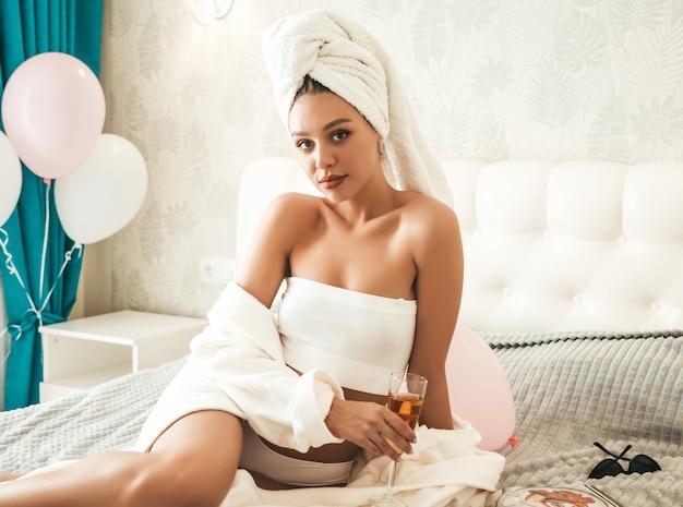 Joven hermosa mujer sonriente en lencería blanca y toalla en la cabeza.