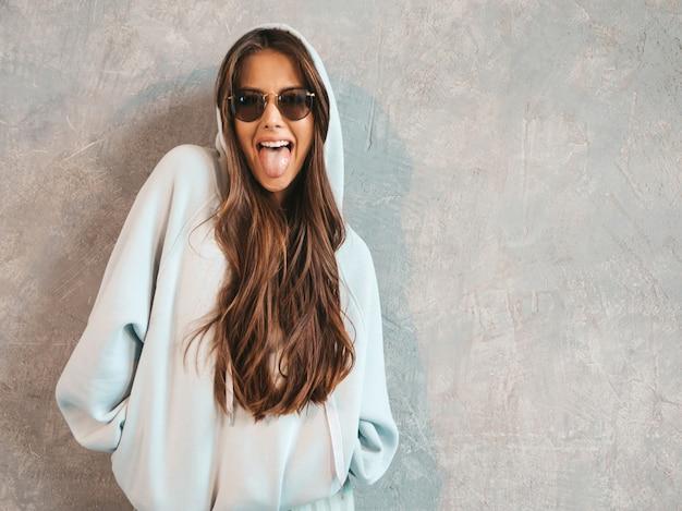 Joven hermosa mujer sonriente mirando. chica de moda en ropa casual de verano con capucha y falda. muestra lengua
