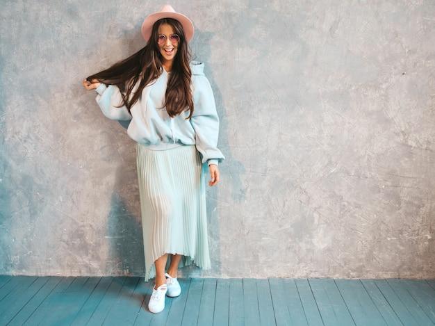 Joven hermosa mujer sonriente mirando. chica de moda en ropa casual de verano con capucha y falda.