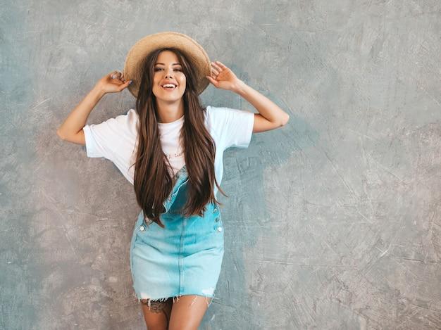 Joven hermosa mujer sonriente mirando. chica de moda en ropa de verano casual monos y sombrero.