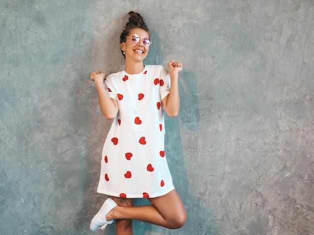 Joven hermosa mujer sonriente mirando. chica de moda en verano casual vestido blanco y gafas de sol. . levantando las manos