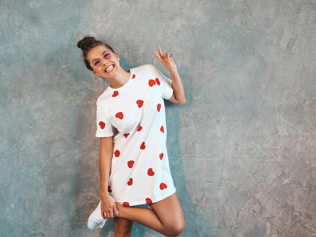Joven hermosa mujer sonriente mirando. chica de moda en verano casual vestido blanco y gafas de sol. . muestra signo de paz