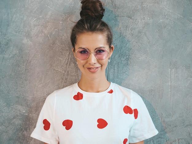 Joven hermosa mujer sonriente mirando. chica de moda en verano casual vestido blanco y gafas de sol.