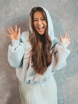 Joven hermosa mujer sorprendida mirando con las manos en el aire. chica de moda en ropa casual de verano. mujer posando junto a la pared gris