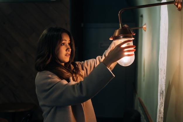 Joven hermosa mujer sostiene en su mano una pequeña lámpara de pared