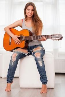 Joven hermosa mujer tocando la guitarra