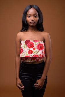 Joven hermosa mujer zulú africana sobre fondo marrón