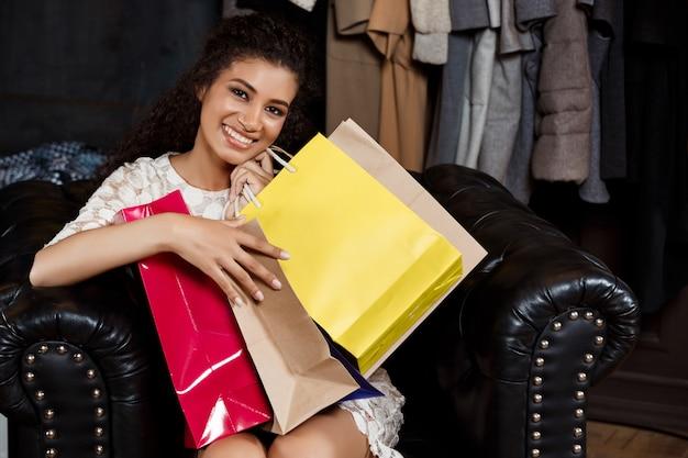 Joven hermosa niña africana sentada en el centro comercial con compras.