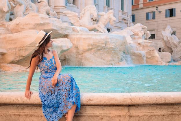 Joven hermosa niña cerca de la fuente fontana di trevi con mapa de la ciudad