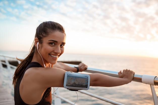 Joven hermosa niña deportiva entrenamiento al amanecer sobre el mar.