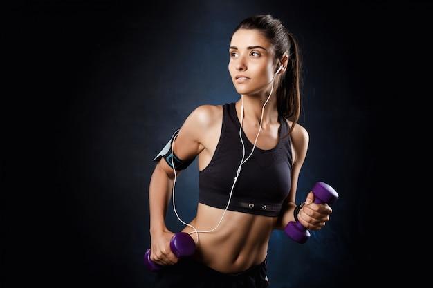 Joven hermosa niña deportiva entrenamiento con pesas sobre la pared oscura.