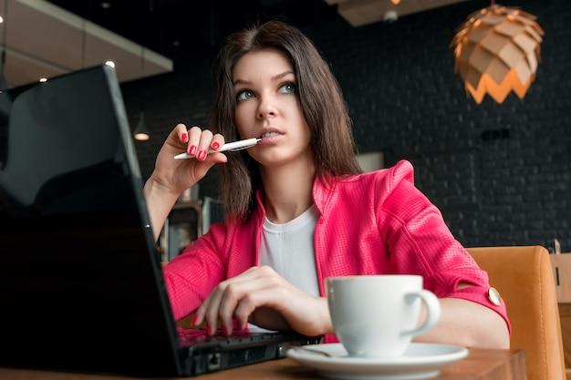 Joven, hermosa niña, empresaria, sentada en la cafetería y trabajando en la computadora portátil