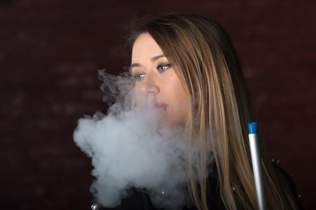 Joven, hermosa niña fuma un narguile