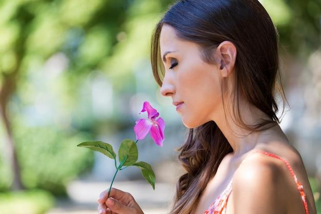 Joven hermosa niña huele flores, contra el jardín de verano verde.