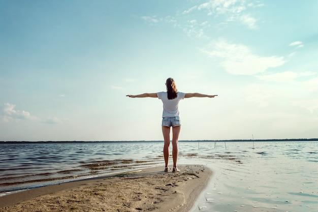 Joven, hermosa niña se levanta contra el cielo y el gran lago