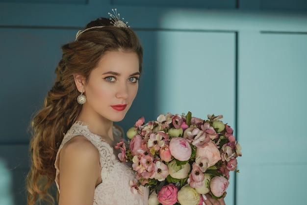 Joven hermosa niña mirando un ramo de flores, novia