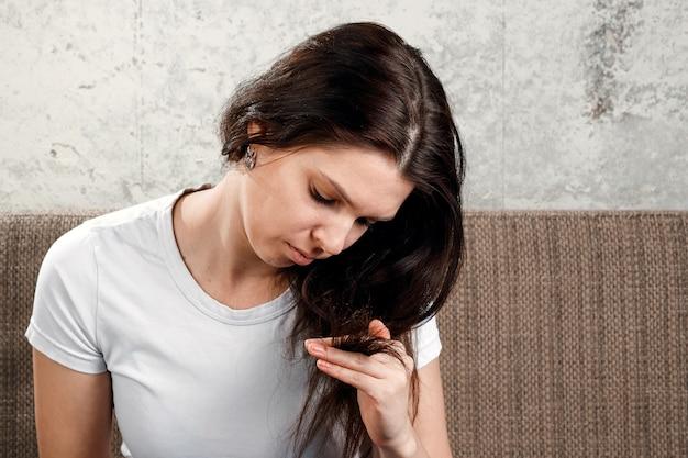 Joven, hermosa niña está nerviosa por la caída del cabello, peinarse, peinarse