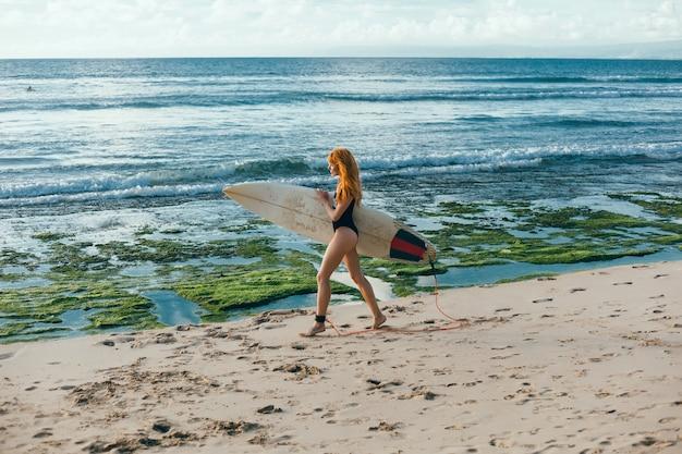 Joven hermosa niña posando en la playa con una tabla de surf, surfista mujer, olas del océano