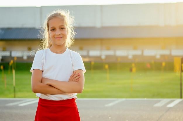 Joven hermosa niña rubia en ropa deportiva una camiseta blanca y pantalones cortos deportivos rojos calentando sobre el asfalto en el estadio. hija activa estirando el cuerpo en la mañana de verano