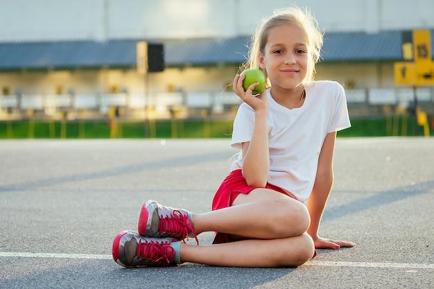 Joven hermosa niña rubia en ropa deportiva una camiseta blanca y pantalones cortos deportivos rojos sentados en el asfalto y comer una manzana verde en el estadio. hija activa para correr en la mañana de verano.
