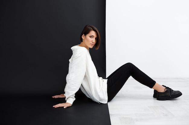 Joven hermosa niña sentada en el piso sobre la pared en blanco y negro